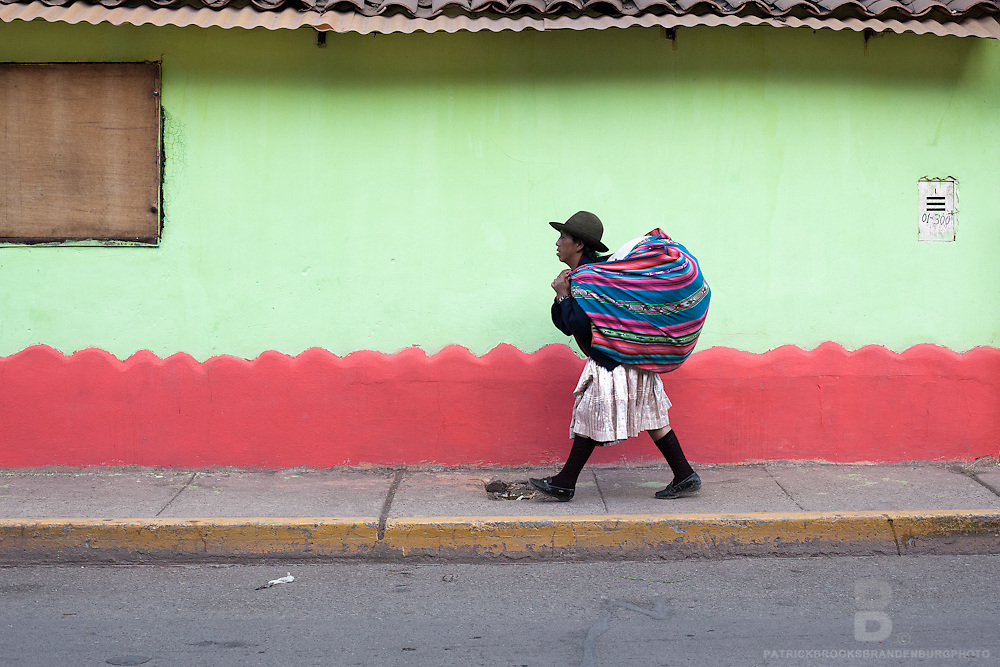 A peruvian women carries a large woven bag on her back while walking agains a lime green wall, wearing tradtional adean clothing and bowlers hat in Pisac, Peru.