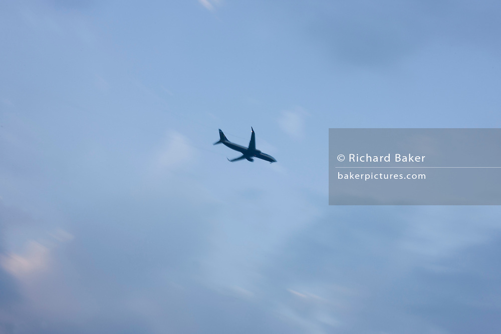 An airliner blurs as it crosses later afternoon sky before landing at local airport.