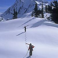 Skiers hike along Shukson Arm near Washington's Mount Baker Ski Area for powder runs below Mount Shuksan (background.)