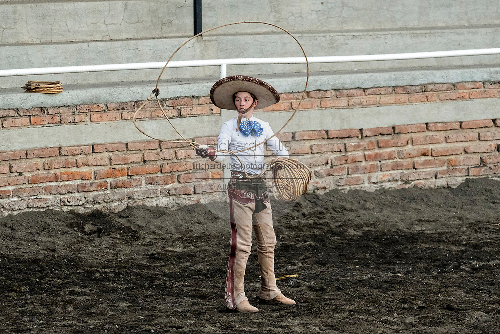 Young Luis Alfonso Franco, from the legendary Franco family of Charro champions performs a roping display before roping a wild horse during a practice session in the Jalisco Highlands town of Capilla de Guadalupe, Mexico. The roping event is called Manganas a Pie or Roping on Foot and involves a charro on foot roping a wild mare by its front legs to cause it to fall and roll once. The wild mare is chased around the ring by three mounted charros.
