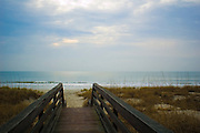 Boardwalk over the dunes that leads to the beach and surf in the early morning hours in Pawleys Island, South Carolina.