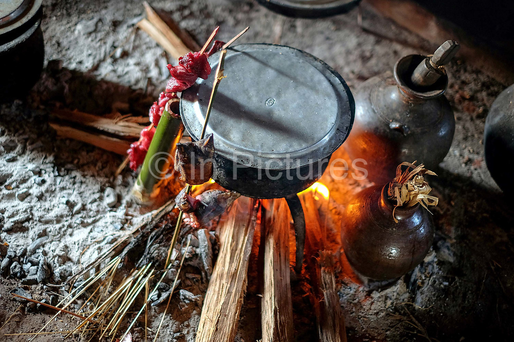 Grilling meat over an open fire in the kitchen of a Kayah (Red Karen) ethnic minority woman village on 18th January 2016 in Kayah State, Myanmar.
