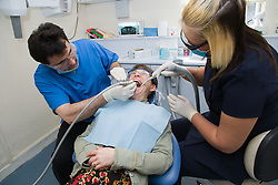 Dentist and dental nurse carrying out dental treatment on a patient,