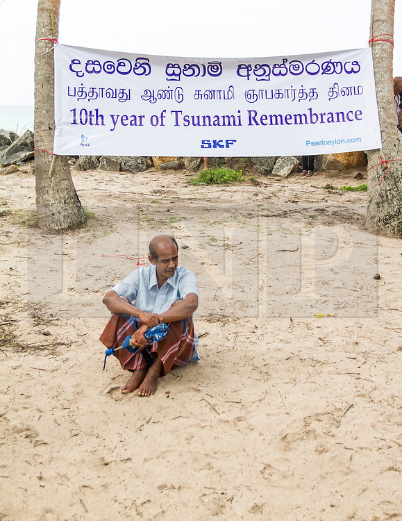 © Licensed to London News Pictures. 26/12/2014. Sri Lanka, UK 10th year commemorations of the Indian Ocean Tsunami, in Sri Lanka. In Peraliya, a man has a moment of reflection during commemorations in remembrance of those that lost their lives or are still missing as a result of the 2004 Indian Ocean Tsunami. Photo credit : Sam Spickett/LNP