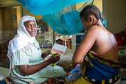 Medical attendant Sophia showing one of the new born checklists. NICU (Neonatal Intensive Care Unit) ward. St Walburg's Hospital, Nyangao. Lindi Region, Tanzania.
