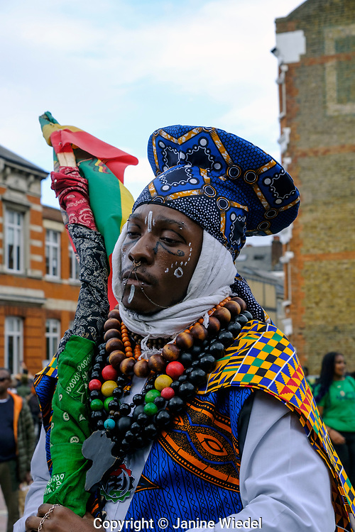 Rastafarian man wearing traditional African clothes at Reparations Rebellion event on Afrikan Emancipation Day in Windrush Square, Brixton 2021.