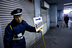 An elderly man works as a security guard, holding a sign of a funeral home in Kamagasaki, Japan. Security guard is one of few jobs that are available to elderly men.