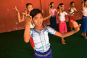 Chanthy wearing her beautiful costume, learns the complicated movements of Khmer Apsara dancing at the School of Beaux Arts.. Chanthy, a young girl, learns the Apsara traditional Khmer dance style, at the School of Beaux Arts outside Phnom Penh. This dance style is particularly inspired by thousands of Apsara statues found at Angkor Wat and performed by the Cambodia Royal Ballet. Chanthy lives with her family in Phnom Penh, her father is a policeman, and her family lives in a municipal apartment block surrounded by other families. Chanthy has good friends including a Chinese girl who is mentally handicapped and lives next door. She loves to visit Phnom Penh city and sites with her mother and father, on his scooter.