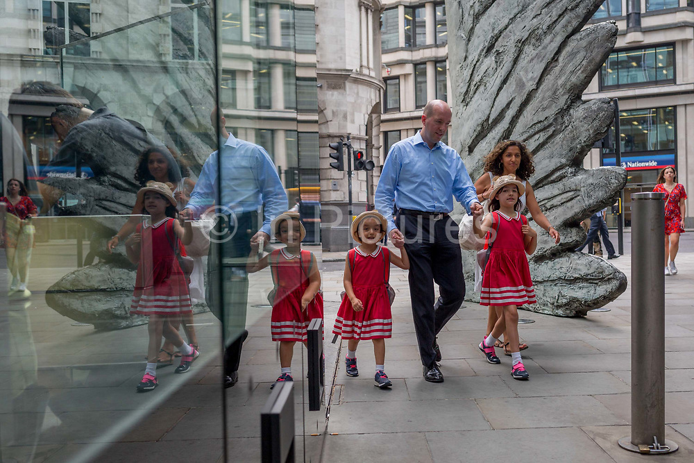 Two youhg girls in matching red dresses are led past the sculpture entitled City Wing on Threadneedle Street in the City of London, the capitals financial district, on 25th July 2018, in London, England. City Wing is by the artist Christopher Le Brun. The ten-metre-tall bronze sculpture is by President of the Royal Academy of Arts, Christopher Le Brun, commissioned by Hammerson in 2009. It is called 'The City Wing' and has been cast by Morris Singer Art Founders, reputedly the oldest fine art foundry in the world.