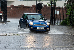 Licensed to London News Pictures. 12/07/2021. London, UK. A car driver gets caught in torrential rain in Richmond Park, southwest London this afternoon with roads and pavements becoming quickly flooded as the Met Office issue yellow weather warnings for heavy rain and thunderstorms which may cause disruption to travel and flooding. However, sunshine and warm weather is predicted for the rest of the week with highs of 26c for the weekend.. Photo credit: Alex Lentati/LNP