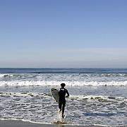 Surfer makes his way into the water at a beach north of Santa Barbara, CA.