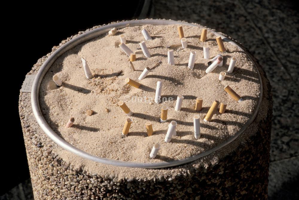 public ashtray full of cigarette butts
