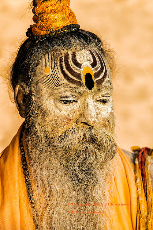 Morning Profile: A napping, saffron dressed Sadhu sits in the golden mornings light with a white beard, white facial paint and a prominent ornate painting that dominates his forehead, Varanasi India.