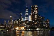 New York skyline at night showing the famous Freedom Tower (in place of the World Trade Centre) and the Hudson River from Pier 25