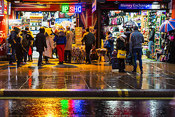 London, December 31 2017. The umbrellas come out as a downpour begins in London's west end ahead of the New Year's Eve fireworks at midnight. PICTURED: Light from shops is reflected in the rain as people take shelter. © SWNS
