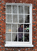 © Licensed to London News Pictures. 14/01/2013. Amersham, UK A woman cleans the inside of a window whilst heavy snow falls outside. People and snow in Amersham in south-east Buckinghamshire. Snow hits the many parts of the UK today 14th January 2013. Photo credit : Stephen Simpson/LNP