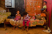 Kids enjoying a leisure time inside a low quality plywood shack in Rosa Leão Occupancy, Isidoro area.
