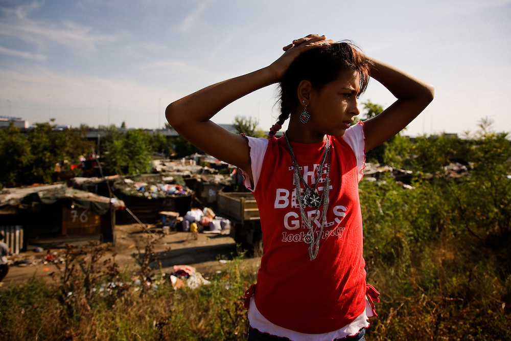 A girl on a hill above the Nova Gazela settlement during the first hours of the relocation. She was waiting for the government trucks to arrive at her home before her family packed their final belongings and set off for a home in the south of Serbia.