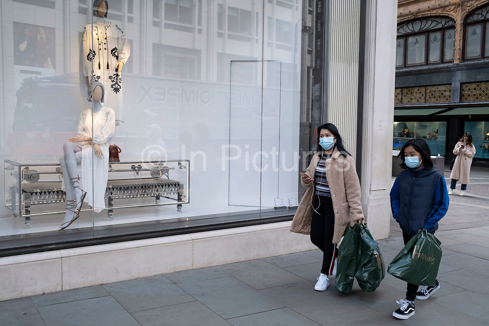 Shopping wearing a face mask and carrying Harrods bags in the upmarket area of Knightsbridge on 14th April 2021 in London, United Kingdom. Knightsbridge is one of the principal areas for exclusive, luxury goods in West London. It is known as a district where the rich and wealthy shop, mostly for high end fashion and jewellery.