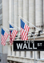 Detail of Wall Street sign with flags on Stock Exchange building to rear Manhattan New York City