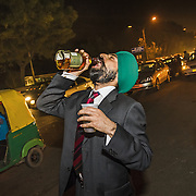 A Sikh participant of the groom's baraat procession makes use of the 'car-bar' which is set outside the venue of the wedding. Delhi 2099
