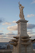 Statue overlooking the water of the harbour at dusk sunset, Havana old town.