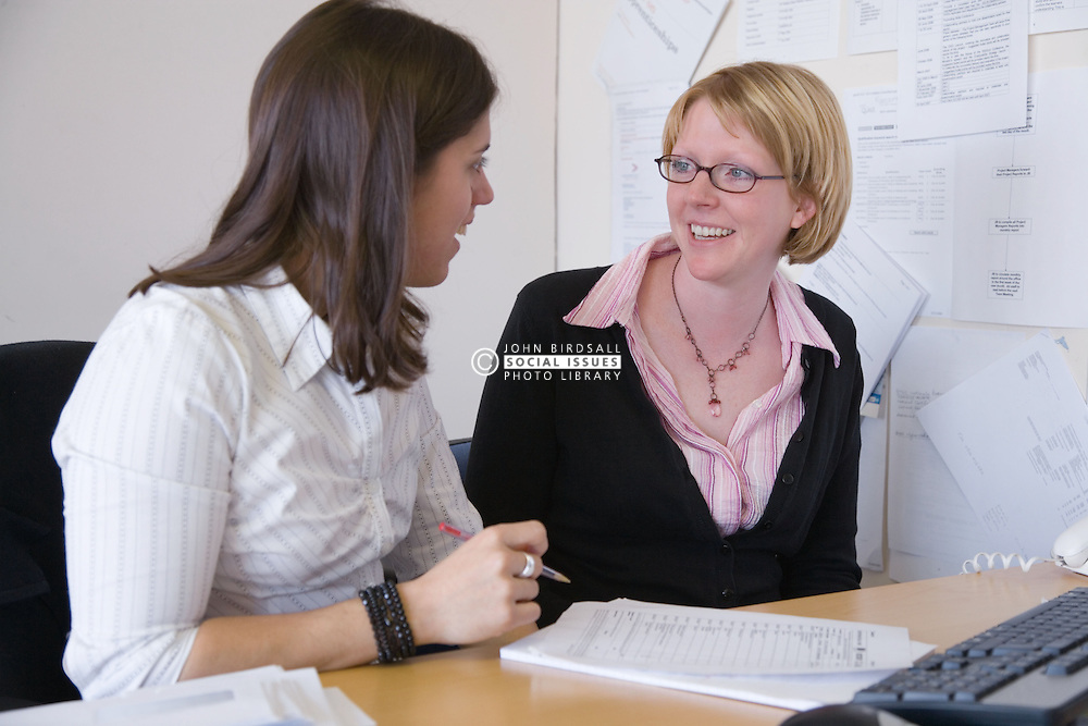 Young women discussing work sitting at a desk,