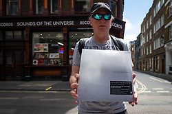 © Licensed to London News Pictures. 12/06/2021. LONDON, UK. Marcelo, a tour guide of iconic music history landmarks for Rockishere,com, shows off his purchase outside Sounds of the Universe Records in Soho on Record Store Day, where independent record shops worldwide celebrate music, including special vinyl releases made exclusively for the day. In the UK, vinyl sales have increased for the 13th consecutive year.  The BPI reported that nearly 5m records were sold in the 2020 in the UK as, with more time spent at home, music lovers had time to add to their collections.  Photo credit: Stephen Chung/LNP