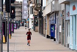 Edinburgh, Scotland, UK. 29 March, 2020. Life in Edinburgh on the first Sunday of the Coronavirus lockdown. Streets deserted, shops and restaurants closed, very little traffic on streets and reduced public transport. Pictured; Princes Street with a lone jogger. Iain Masterton/Alamy Live News