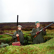 A 'gun' and his loader waiting in a shooting butt on a grouse shoot, Bransdale Moor, North York Moors, North Yorkshire, UK