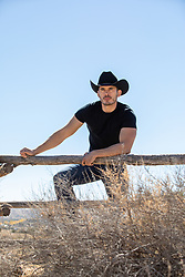 attractive cowboy leaning on a rustic fence