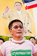 """Apr. 2, 2010 - BANGKOK, THAILAND: A supporter of the Thai monarchy holds up a photo of the King during a Pink Shirt protest in Bangkok Friday. Thousands of """"Pink Shirts,"""" who claim to be neither """"Red Shirts"""" nor """"Yellow Shirts"""" nicknames for Thailand's dueling political forces, gathered in Lumpini Park in central Bangkok Friday evening to call for """"peace in the land,"""" a play on the Red Shirts slogan, """"Red in the Land."""" The """"Pink Shirts"""" represented educators, business people and people in the tourist industry, all of which have been hurt by the ongoing political protests that have disrupted life in the Thai capital. The """"Pink Shirts"""" stressed their loyalty to His Majesty Bhumibol Adulyadej, the King of Thailand, and chanted for the Red Shirts to """"Get Out!"""" of Bangkok.    PHOTO BY JACK KURTZ"""