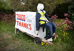 © Licensed to London News Pictures. 27/04/2020. Capel, UK. A scarecrow depiction of a Tesco delivery driver stands at the front of a house in the Surrey village of Capel. Residents of the village have resurrected their summer tradition of scarecrows in tribute to NHS medical staff and other key workers. Up to 30 of the life size home made doll like characters can be seen in front gardens throughout the village. The public have been told they can only leave their homes when absolutely essential, in an attempt to fight the spread of coronavirus COVID-19 disease. Photo credit: Peter Macdiarmid/LNP