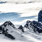 Rugged rocky mountains covered in snow and ice rise up from the Antarctica Peninsula near Cuverville Island.