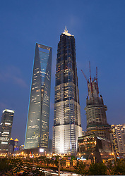 Evening view of World Financial Center (left) JinMao Tower (center) and Shanghai Tower under construction in Lujiazui Pudong Shanghai China