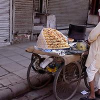 Asia, India, New Delhi. Scene of life in Old Delhi, baker selling Indian bread snacks.