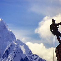 A sherpa practices rappelling  at an early mountaineering school for sherpas in the Khumbu region of Nepal, 1980. Mt. Ama Dablam bkg.