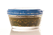 A small jar of home made pesto (stored in a caviar jar and lid with Japanese instructions on the rim).