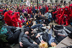 London, UK. 14 October, 2019. Climate activists from Extinction Rebellion, including one representing Boris Johnson wearing a blonde wig, stage a die-in in front of the Bank of England following theatrical mock trials of the UK's financial sector for the crime of ecocide and of the Government for 'criminal negligence' in having permitted it. Roads were blocked around Bank on the eighth day of International Rebellion protests across London.