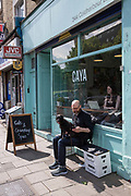 A man looking at his mobile phone with a dog on his lap outside a coffeeshop on Coldharbour Lane on the 23rd May 2019 in London in the United Kingdom.