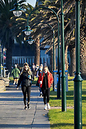 A pair of women walk along the foreshore in Port Melbourne which is now a listed COVID hot spot in Melbourne on the 7th day the state wide COVID-19 lockdown that has been placed on the State of Victoria. (Photo by Michael Currie/Speed Media)