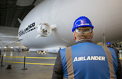 © Licensed to London News Pictures. 21/03/2016. Bedford, UK. The fully completed Airlander 10 hybrid airship is unveiled at Cardington.  This is the largest aircraft currently flying. It uses innovative technology to combine the characteristics of fixed wing aircraft and helicopters with lighter-than-air technology to create a new breed of hyper-efficient aircraft. It can stay airborne for up to five days at a time if manned, and for over 2 weeks unmanned. It will fulfil a wide range of communication, cargo carrying and survey roles in both the military and commercial sectors all with a significantly lower carbon footprint than other forms of air transport. Photo credit: Peter Macdiarmid/LNP
