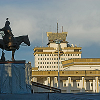 A statue of a Mongolian warrior stands beside steps leading to the Parliament building (not visible) and above Sukhbaatar Square. Other government buildings lie in the background.