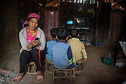 A mother plays music from her cellphone while her son and two of his friends watch television at home in Ban Sop Kha, Laos. The electronics are powered by batteries (right) charged by micro hydro turbines jury-rigged into the Nam Ou River.