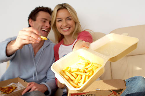 couple sitting on sofa eating pizza and chips, offering chips towards camera, fast food,<br />