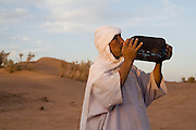 Camel guide Elhussein Sbiti takes a drink of water from his gourd on a three-day camel trek to the remote sand dunes of Erg Zehar, near M'hamid in the Moroccan Sahara. Sbiti, like many berber nomads in the region, has found opportunity in the new tourism trade burgeoning since the settling of tensions between Morocco and neighboring Algeria..
