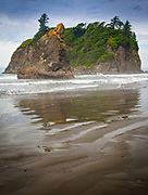 """Ruby Beach is the northernmost of the southern beaches in the coastal section of Olympic National Park. It is located on Highway 101, in Jefferson County, 27 miles south of the town of Forks, Washington. Per National Park Service, Ruby Beach is """"Not in Park but right on edge.""""  Like virtually all beaches on the northern coast, Ruby Beach has a tremendous amount of driftwood. It is notable for the number of sea stacks there."""