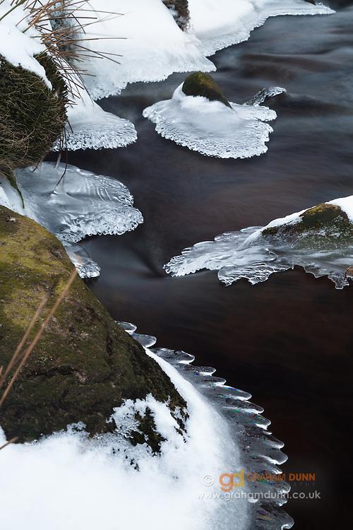 Ice patterns decorate the rocks in Burbage Brook just before it passes under Burbage Bridge. Peak District, Derbyshire, England, UK.