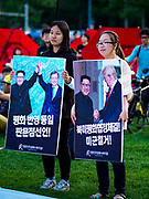"15 JUNE 2018 - SEOUL, SOUTH KOREA: South Korean teenagers, one with a placard honoring the inter Korean summit between North Korean leader Kim Jong-un and South Korean President Moon Jae-in, the other holding a placard honoring the Singapore Summit between Kim and US President Donald Trump during a rally to mark the anniversary of the signing of the June 15th North–South Joint Declaration between South Korea and North Korea. The Declaration was negotiated by late South Korean President Kim Dae-jung and North Korean leader Kim Jong-il and signed on 15 June 2000. It was a part of South Korea's ""Sunshine Policy,"" which guides the South's relationship with North Korea. This year's observance of the anniversary was bolstered by the recent thawing in relations between North Korea and South Korea and the US.    PHOTO BY JACK KURTZ"