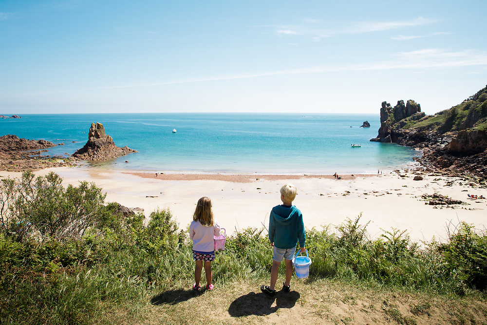 Children holding buckets looking out at the calm clear water, sand and rocks at Beauport beach on a sunny spring day in Jersey, Channel Islands